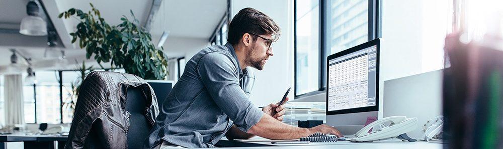 Angestellter sitzt vor dem Computer und erledigt die Buchhaltung